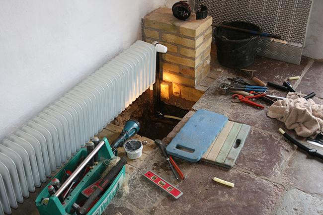 Billede af hul, der hvor radiatorrørerne går ned i gulvet.