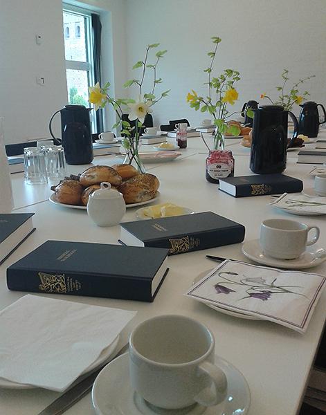 Billede af opdækket kaffebord, med blomster, sangbøger og rundstykker.
