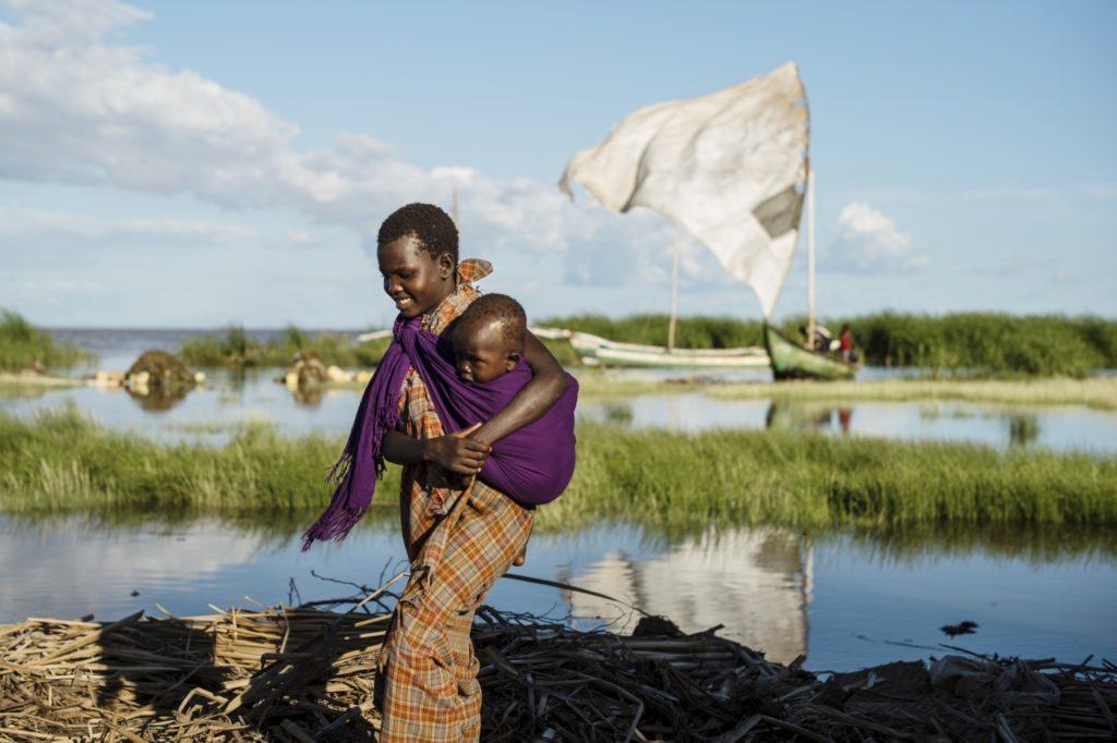 Ung kvinde med sin yngre søster på armen, går i et vandområde